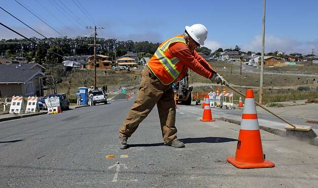PG&E workers sweep dirt as they  fill over a distribution gas line on Glenview Dr. in San Bruno on Thursday August 11, 2011,  near the site of last year's blast. Photo: Lacy Atkins, The Chronicle
