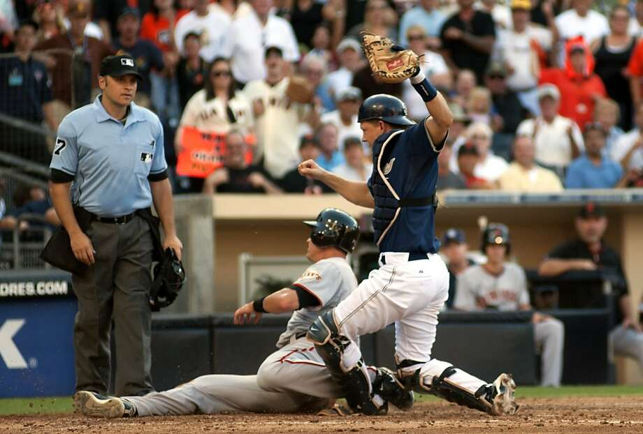 San Diego Padres catcher Nick Hundley, right,makes the tag out at home plate of San Francisco Giants' Brett Pil, center, during the seventh inning of a baseball game at Petco Park on Wednesday, Sept. 7, 2011, in San Diego. (AP Photo/ Kent C. Horner) Photo: Kent C. Horner, AP