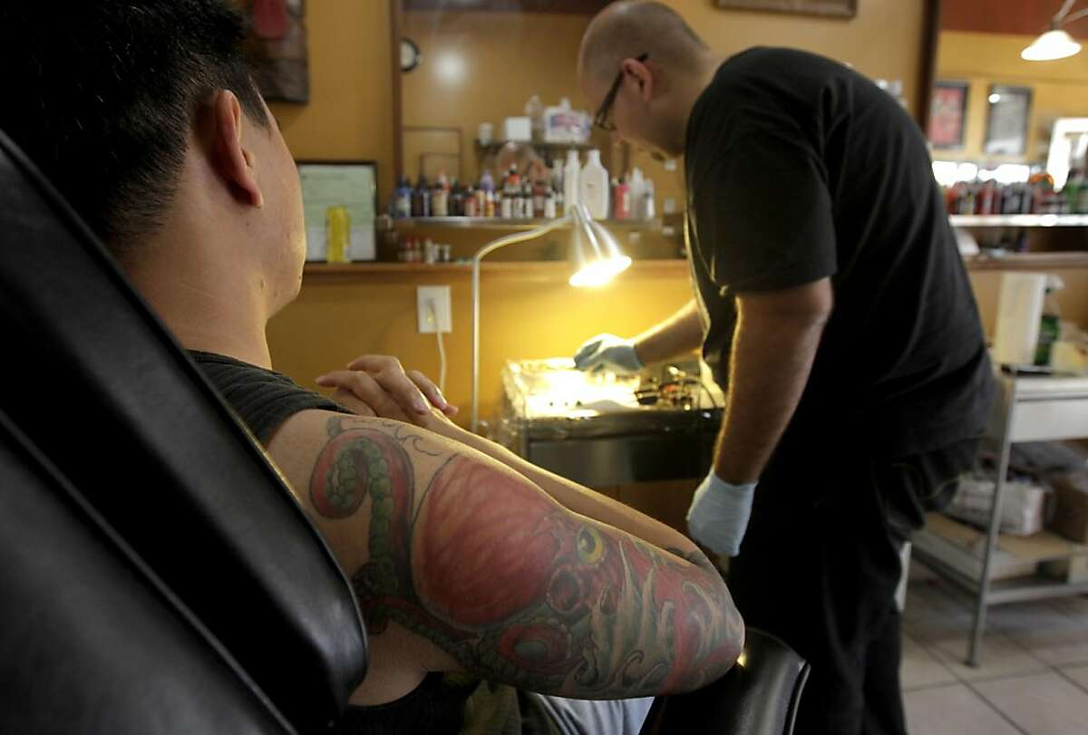 Vien Tang watches Mario Delgado prepare ink for Tang's octupus tattoo at the Moth and Dagger tattoo studio in San Francisco, Calif. on Saturday, Sept. 3, 2011. Tattoo studios are not required to post ingredients in the inks used but tattoo artist Delgado will provide them on request.
