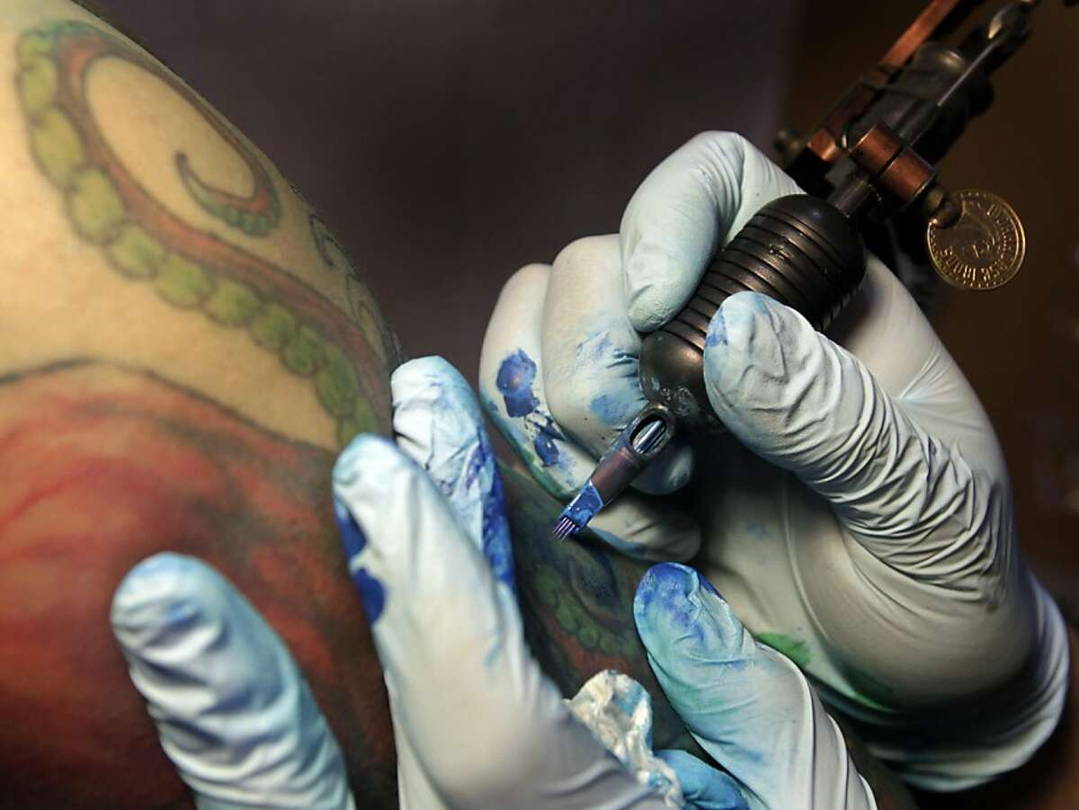 Mario Delgado (right) applies ink to a tattoo of an octupus for Vien Tang at the Moth and Dagger tattoo studio in San Francisco, Calif. on Saturday, Sept. 3, 2011. Tattoo studios are not required to post ingredients in the inks used but tattoo artist Delgado will provide them on request.