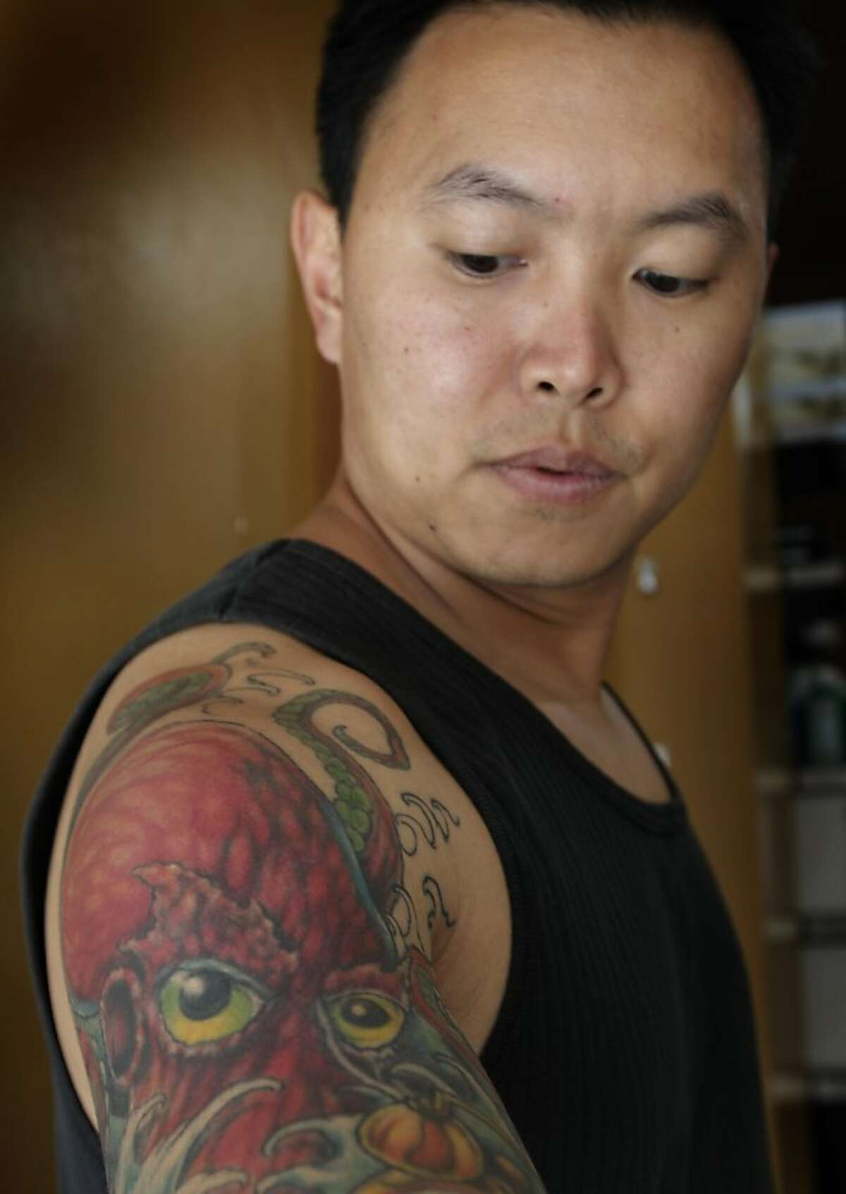 Vien Tang takes a close look at his octopus tattoo created by Mario Delgado at the Moth and Dagger tattoo studio in San Francisco, Calif. on Saturday, Sept. 3, 2011. Tattoo studios are not required to post ingredients in the inks used but Delgado, a tattoo artist and the studio's owner, will provide them on request.