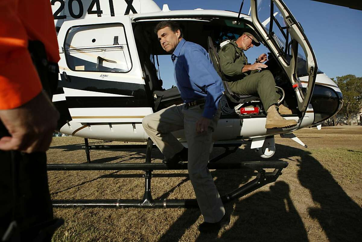 AUSTIN, TX - SEPTEMBER 6: Republican presidential candidate and Texas Gov. Rick Perry (L) steps out of a Texas Department of Public Safety helicopter after an aerial tour of the area around Steiner Ranch where homes were destroyed by wildfires the last two days September 6, 2011 in Austin, Texas. Perry, who left his presidential campaign to respond to the fires, said more than 1,000 houses in the area were destroyed. (Photo by Erich Schlegel/Getty Images)