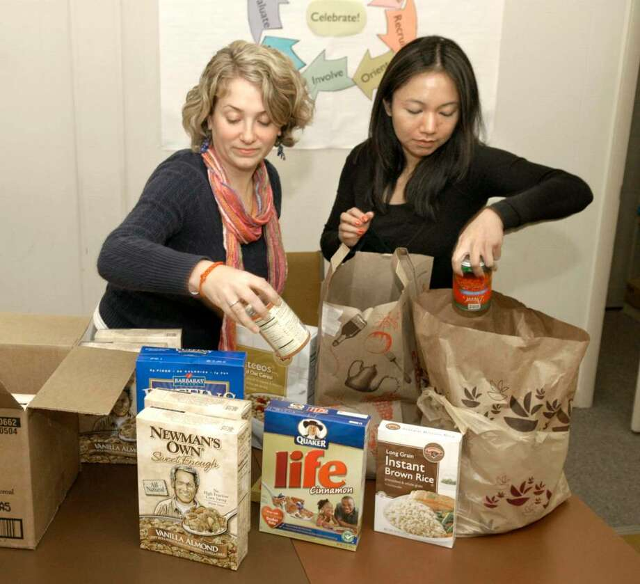 """Jessica McKeown, 24,of left amd Zobel Belisario, 22, of New Fairfield with food that will used for """"Fill the Wall-Feed the Hungry"""" Friday at the Danbury Fair Mall. Photo: Carol Kaliff / The News-Times"""