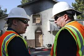 PG&E Customer Relations Supervisor Bruce Pitcher, left, speaks with PG&E Gas Service Supervisor Xavier De La Rocha infront of a home that was destoryed by a gas fire the night before on Thursday, September 1, 2011 in Cupertino, Calif.