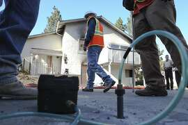 PG&E representatives inspect underground gas lines surrounding the home that caught on fire the night before on Thursday, September 1, 2011 in Cupertino, Calif.