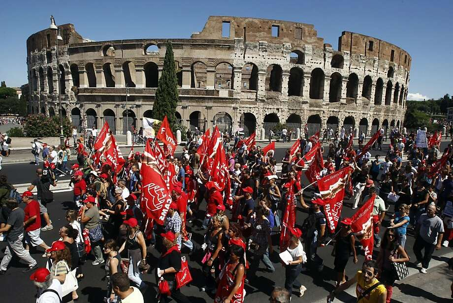 Demonstrators march past the Colosseum during a general strike in Rome, Tuesday, Sept. 6, 2011. With Silvio Berlusconi's government under increasing pressure to produce credible measures to balance the budget, a strike by Italy's largest labor union against an austerity package shut down air, land and sea transport, stalled manufacturing and curtailed government services throughout the country on Tuesday. Susanna Camusso, head of the left-leaning CGIL, said the euro 45.5 billion ($68 billion) austerity package needs to be thrown out and substituted with fairer measures. (AP Photo/Pier Paolo Cito) Photo: Pier Paolo Cito, AP