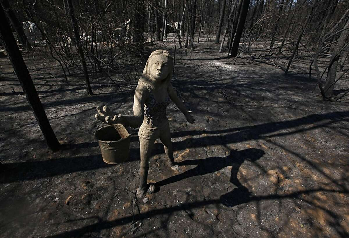 BASTROP, TX - SEPTEMBER 6: A statue of a woman holding a water bucket stands in front of the remnants of a burned down home on the east side of Lake Bastop on September 6, 2011 outside Bastrop, Texas. Several large wildfires have been devastating Bastrop County for the last two days. (Photo by Erich Schlegel/Getty Images)