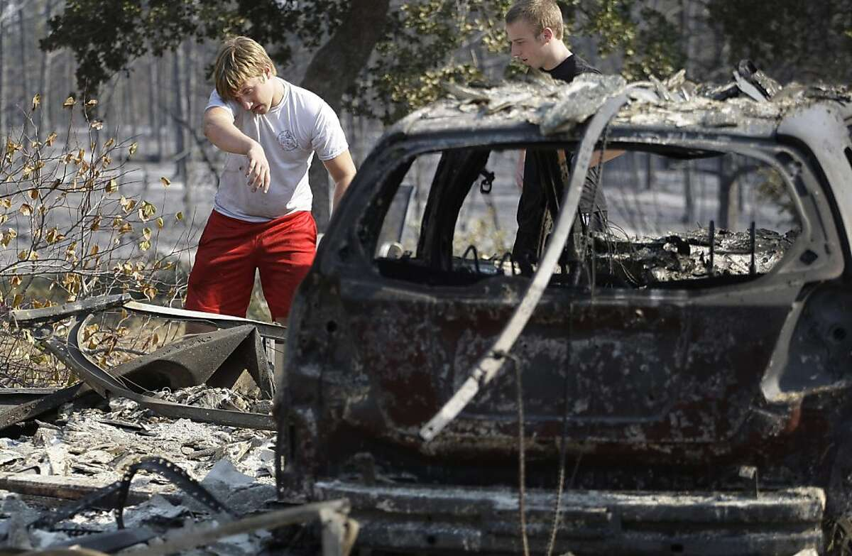Hayden Wilhelm, left, sprays water on hot spots at a neighbors home that burned when wildfires swept through the area, Tuesday, Sept. 6, 2011, in Bastrop, Texas. More than 1,000 homes have burned in at least 57 wildfires across rain-starved Texas, officials said Tuesday. (AP Photo/Eric Gay)