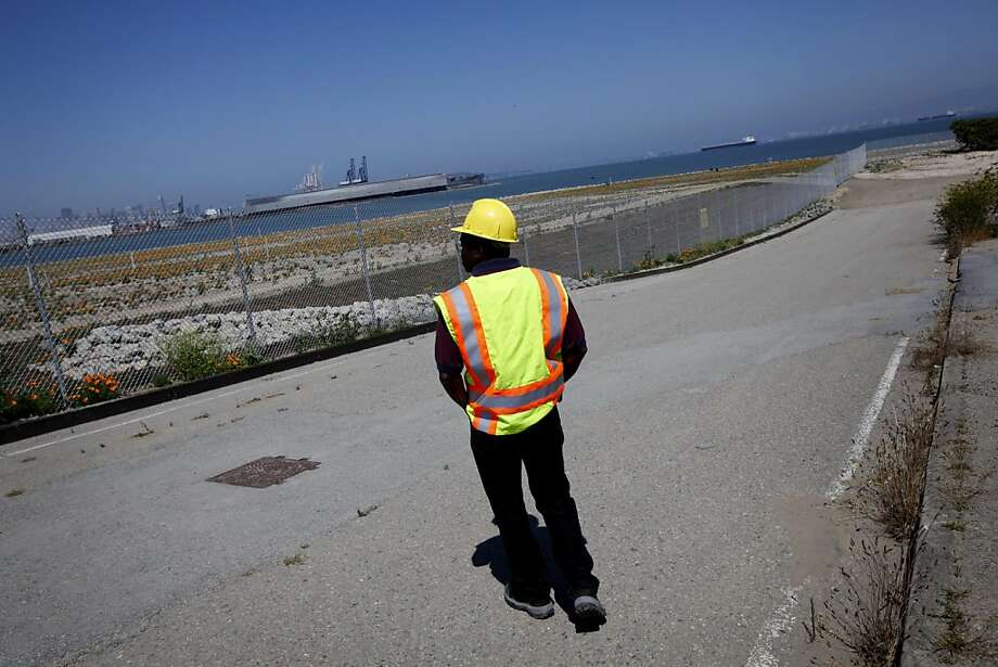 Matt Robinson, the Navy's community involvement manager, surveys a parcel of land at Hunter's Point Naval Shipyard in San Francisco, Calif., Thursday, September 1, 2011.  The Navy has been working with the EPA to clean up the toxic site. The area beyond the fence, which they have been working to decontaminate since 1997, will be ready to transfer to the community in 2012. Photo: Sarah Rice, Special To The Chronicle