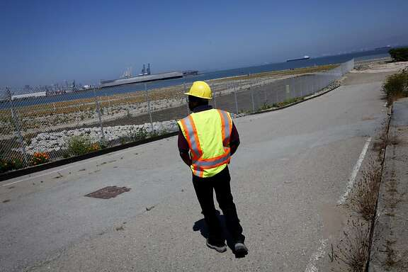 Matt Robinson, the Navy's community involvement manager, surveys a parcel of land at Hunter's Point Naval Shipyard in San Francisco, Calif., Thursday, September 1, 2011.  The Navy has been working with the EPA to clean up the toxic site. The area beyond the fence, which they have been working to decontaminate since 1997, will be ready to transfer to the community in 2012.