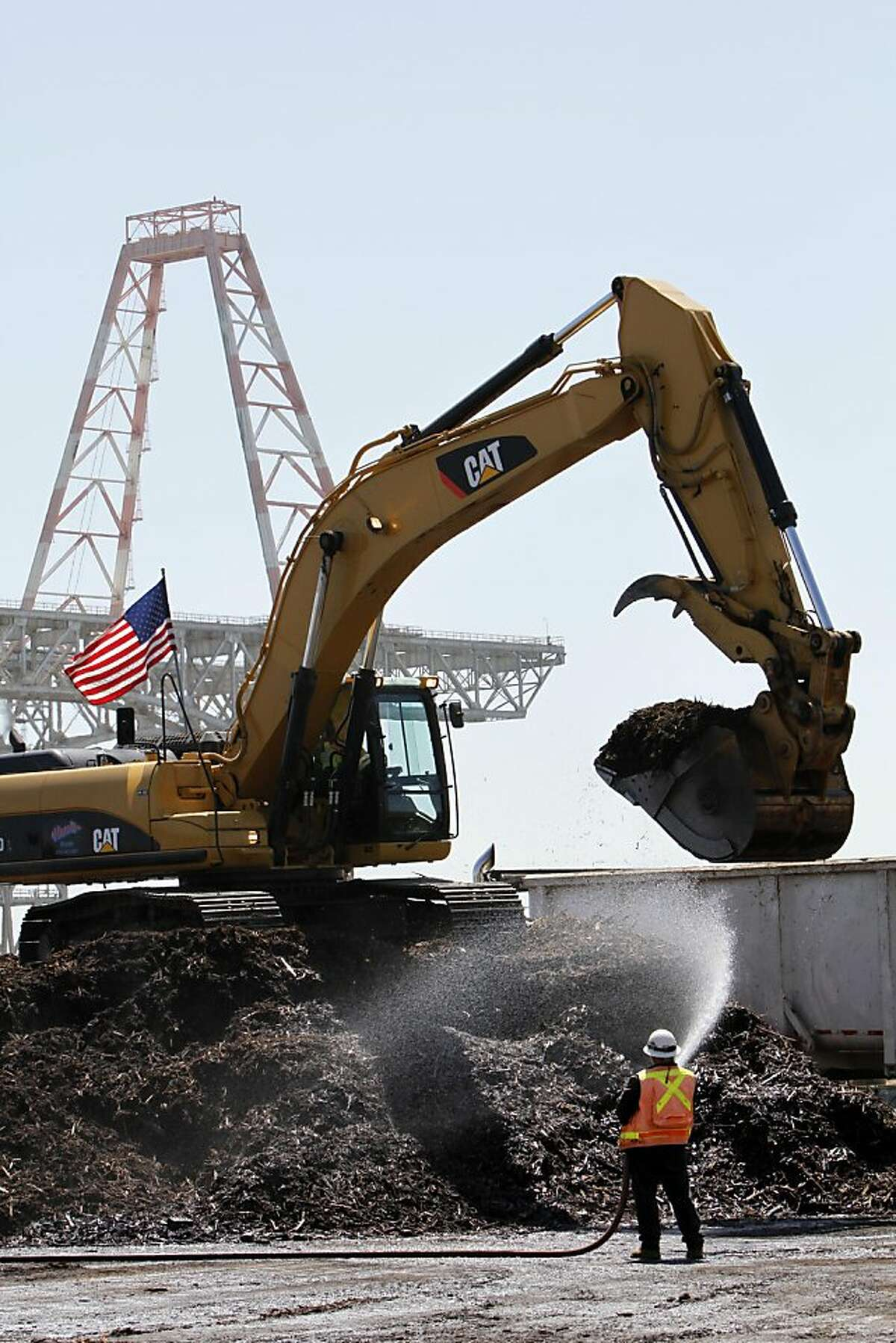 A worker sprays down piles of mulch created from dismantling old piers at Hunter's Point Naval Shipyard in San Francisco, Calif., Thursday, September 1, 2011. The Navy has been working with the EPA to clean up the toxic site.