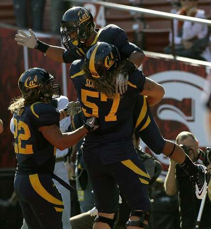 California running back Isi Sofele, top, celebrates with fullback Will Kapp (22) and offensive linesman Brian Schwenke (57) after scoring a touchdown against Fresno State in the first quarter of an NCAA college football game in San Francisco, Saturday, Sept. 3, 2011. (AP Photo/Jeff Chiu) Photo: Jeff Chiu, AP