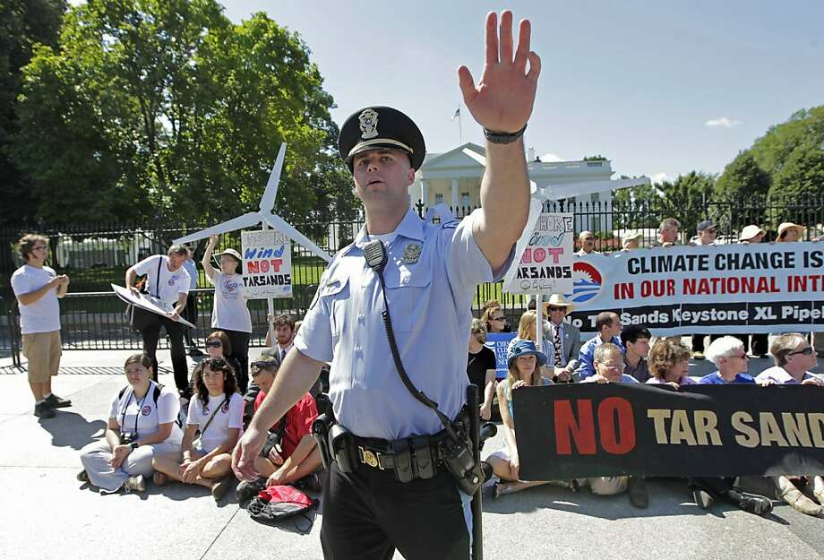 A U.S. Park Police officer motions journalists away from a group of environmental activists gathered outside the White House in Washington, Monday, Aug. 22, 2011, during a civil disobedience campaign against a proposed oil pipeline that would run from Canada to the U.S. Gulf Coast. The protesters want President Barack Obama to deny a permit for the 1,700-mile Keystone XL pipeline that would take oil extracted from tar sands in Alberta, Canada, and carry it through a pipeline cutting across Montana, South Dakota, Nebraska, Kansas, Oklahoma and Texas to refineries in Houston and Port Arthur, Texas.   (AP Photo/J. Scott Applewhite) Photo: J. Scott Applewhite, AP