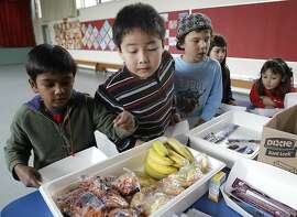 Fairmeadow Elementary School second grade student Jonathan Cheng, center, looks at fruits and vegetables during a school lunch program in Palo Alto, Calif., Thursday, Dec. 2, 2010. More children would eat lunches and dinners at school under legislation passed Thursday by the House and sent to the president, part of first lady Michelle Obama's campaign to end childhood hunger and fight childhood obesity. The $4.5 billion bill approved by the House 264-157 would expand a program that provides full meals after school to all 50 states. It would also try to cut down on greasy foods and extra calories by giving the government power to decide what kinds of foods may be sold in vending machines and lunch lines. (AP Photo/Paul Sakuma) Ran on: 12-03-2010 Student Jonathan Cheng checks out healthy options at Fairmeadow Elementary School in Palo Alto.