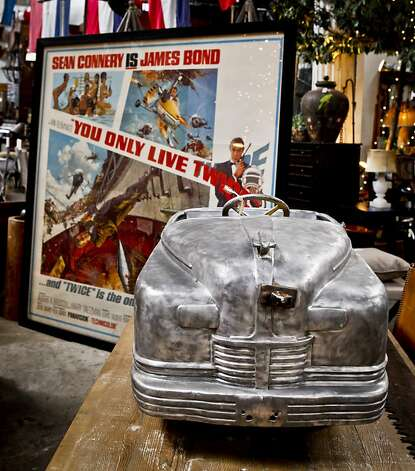 A 1967 James Bond movie ad and an antique car from Coney Island are seen in Big Daddy's Antiques on Monday, Aug. 1, 2011 in San Francisco, Calif. Photo: Russell Yip, The Chronicle