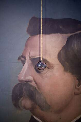 A monocle hangs in front of an oil portrait whose subject appears to be peering through it at The Perish Trust. Photo: Kelly Ishikawa/Rod Hipskind Styl
