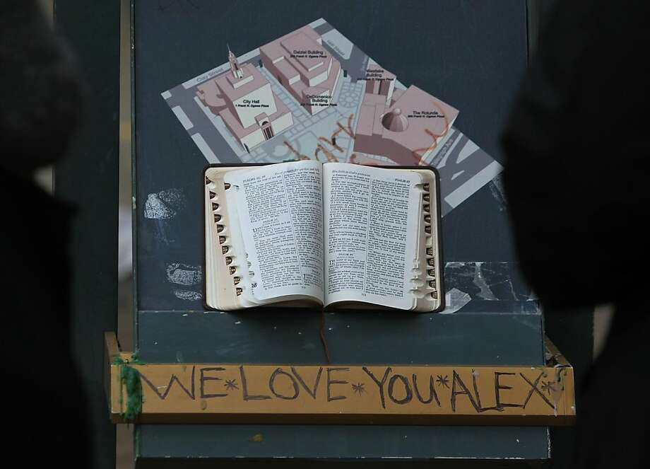 People stop to read a Holy Bible at a memorial for a young man, murdered at the site the night before, in front of the Occupy Oakland encampment in Oakland, Calif. on Friday, Nov. 11, 2011. Photo: Paul Chinn, The Chronicle
