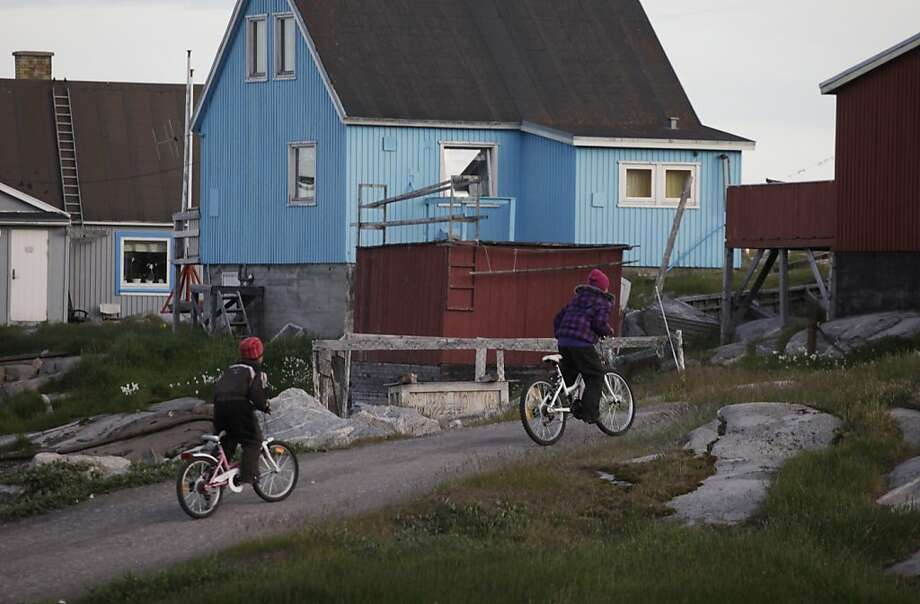 ADVANCE FOR USE SUNDAY, AUG. 21, 2011 AND THEREAFTER - In this July 21, 2011 photo, daughters of Greenlandic Inuit hunter Nukappi Brandt, Aaneeraq, 9, right, and Luusi, 8, ride their bicycles home late at night after an unsuccessful seal hunt with their father in Qeqertarsuaq, Disko Island, Greenland. Roughly 20 years ago, Brandt says, when winter sea ice became too thin to support dogsleds, seal hunting ceased to be a sustainable way of life here. (AP Photo/Brennan Linsley) Photo: Brennan Linsley, AP