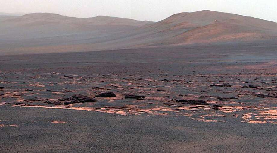 This Aug. 9, 2011 image provided by NASA shows a view from the Mars Rover Opportunity from the Western rim of the Endeavour Crater. This crater -- with a diameter of about 14 miles -- is more than 25 times wider than any that Opportunity has previously approached during the rover's 90 months on Mars. (AP Photo/NASA) Photo: AP