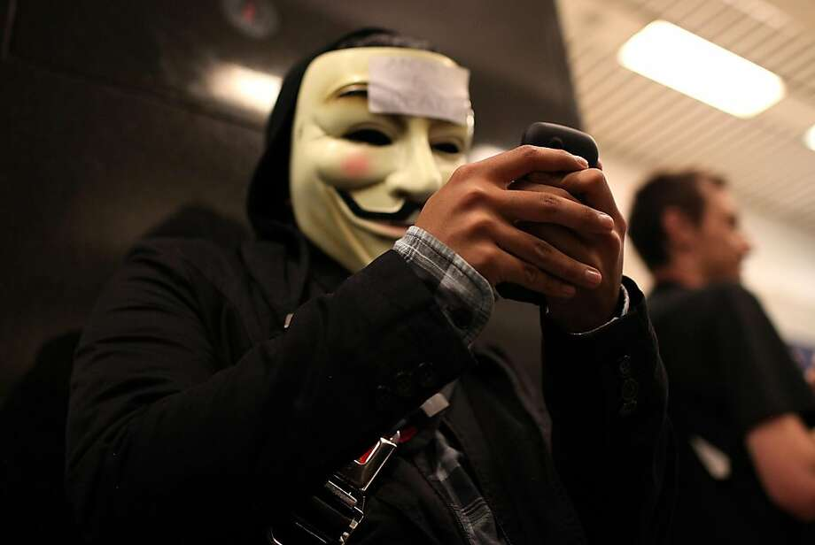 "SAN FRANCISCO, CA - AUGUST 15:  A demonstrator wears a mask as he tries to use his cell phone during a protest inside the Bay Area Rapid Transit (BART) Civic Center station on August 15, 2011 in San Francisco, California.  The hacker group ""Anonymous"" staged a demonstration at a BART station this evening after BART officials turned off cell phne service in its stations last week during a disruptive protest following a fatal shooting of a man by BART police.  (Photo by Justin Sullivan/Getty Images) Photo: Justin Sullivan, Getty Images"