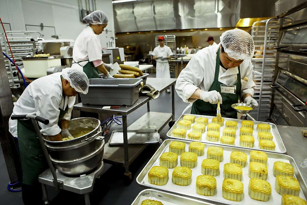 Chi Chao Chang, right, coats partially cooked mooncakes with egg before browning them in the oven for Koi Palace restaurant at Magic Gourmet Trading Inc. in Millbrae, Calif., on Tuesday, Aug. 23, 2011. Ran on: 09-01-2011 Chi Chao Chang (right) brushes egg on mooncakes at Koi Palaces Millbrae facility. The dim sum restaurant makes 15,000 boxes a year.