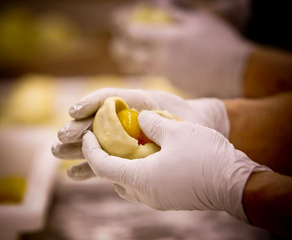 Ya Cai Lin helps stuff mooncakes with two egg yolks at Magic Gourmet Trading Inc. in Millbrae, Calif., on Tuesday, Aug. 23, 2011.