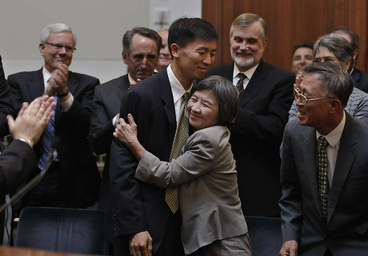 University of California, Berkeley law professor Goodwin Liu, center, is hugged by his mother Yang Ching Liu as he father, Wen Pen Liu, right, looks on after he was confirmed as an Associate Justice by a three member appointment board of the Commission on Judicial Appointments in San Francisco, Wednesday, Aug. 31, 2011. (AP Photo/Paul Sakuma)