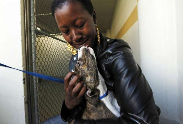 "Shwanna Edwards hugs her newly adopted pit-bull mix that they named Madeline at the San Francisco Animal Care and Control office Thursday September 1, 2011 in San Francisco, California. The Shelter is over running with abandoned and surrendered animals do to the economy, so they are holding a half ""Labor of Love"" sale. Photo: Lance Iversen, The Chronicle"