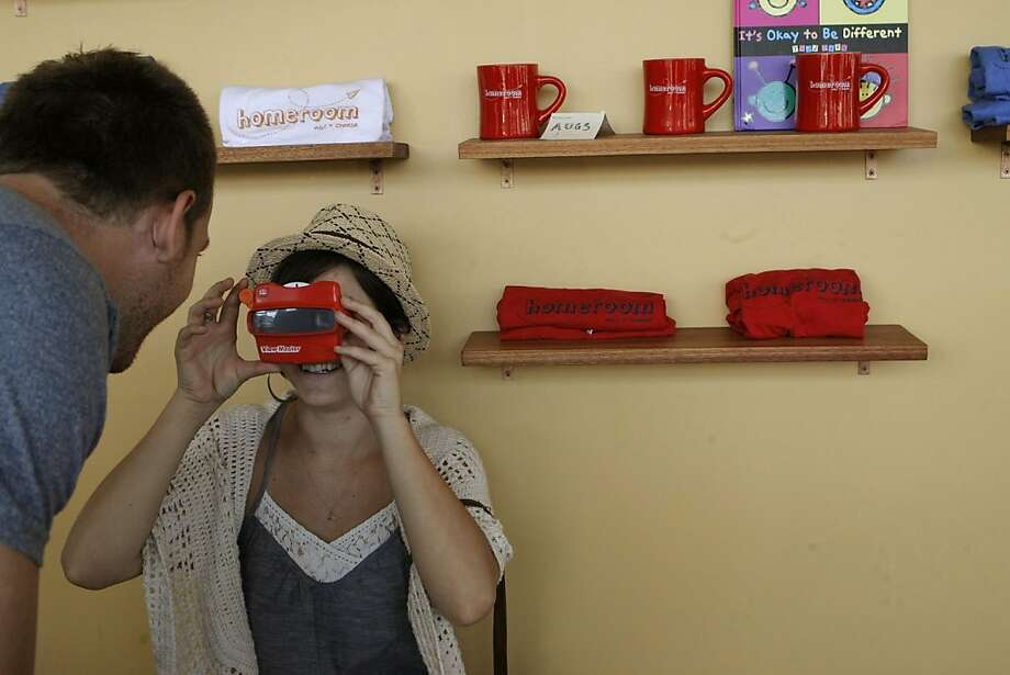 Joanna Andreoni plays with a kids View Master toy while waiting as Jared Berry picks up their order to go from Homeroom in Oakland Calif.,  on August 31, 2011.  Because of the current state of the economy, many bay area residents are choosing to remain at home rather than go on vacation for Labor Day, bringing restaurants like Homeroom more business over the holiday weekend. Photo: Audrey Whitmeyer-Weathers, The Chronicle