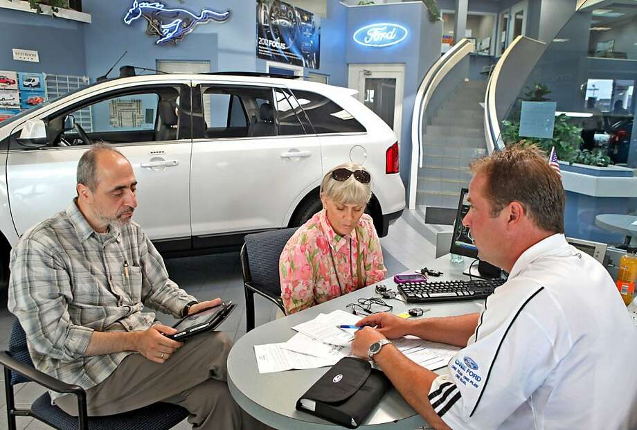 Steven Ambrose, a Golf Mill Ford Motor Co. sales representative, right, speaks with customers at the dealership in Niles, Illinois, U.S., on Wednesday, Aug. 31, 2011. U.S. auto sales failed to rebound in August as confidence sank and prospects dimmed for faster economic growth, prompting at least a dozen analysts to lower estimates for light-vehicle deliveries for this year and next. Photographer: Tim Boyle/Bloomberg *** Local Caption *** Steven Ambrose Photo: Tim Boyle, Bloomberg