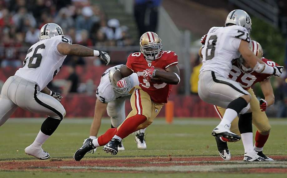 San Francisco 49ers running back Xavier Omon (33) runs for a first down in the fourth quarter, chased by Oakland Raiders linebacker Darryl Blackstock (56) and defensive end Tommie Hill (78), as the San Francisco 49ers take on the Oakland Raiders in preseason action at Candlestick Park in San Francisco, Calif. on Saturday August 20, 2011. Photo: Michael Macor, The Chronicle