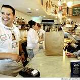 Manager Julio de la Cruz helps customers during busy lunch time rush at Genova Delicatessen and Ravioli Factory.