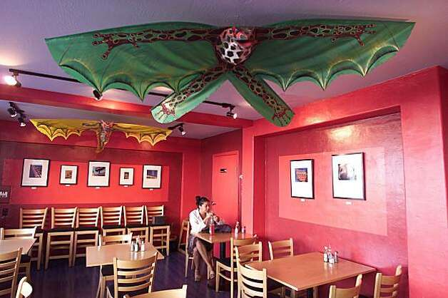 WBLUNCH02A-25OCT01-SF-BW--The dining area of Papalote Mexican Grill on 24th Street features bright colors and photographs of neighborhood signs. By Brant Ward/Chronicle Photo: Brant Ward, The Chronicle