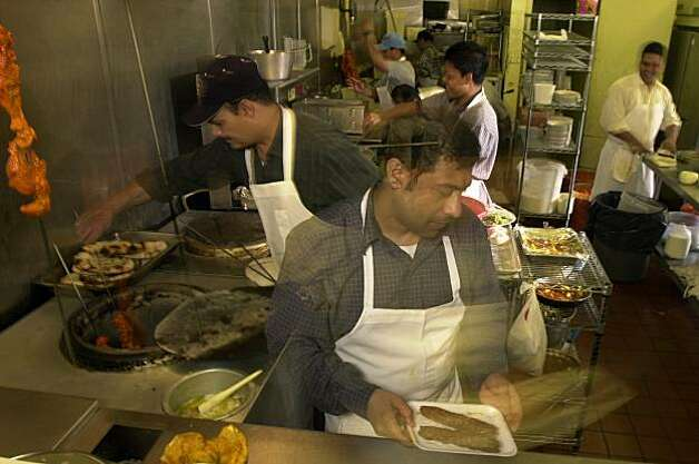 INDIAN016 la.jpg Azhar Ikram serves up a dish during the busy lunch time at the Shalimar Indian Restaurant  in the Tenderloin .06/12/03 in San Francisco.  LACY ATKINS / The Chronicle   Ran on: 04-26-2007 (PN, EB, NB ZONES) The kitchen staff at  Shalimar is quick-paced during lunchtime at the Indian restaurant in the Tenderloin. Photo: Lacy Atkins, SFC