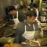 INDIAN016 la.jpg Azhar Ikram serves up a dish during the busy lunch time at the Shalimar Indian Restaurant  in the Tenderloin .06/12/03 in San Francisco.  LACY ATKINS / The Chronicle   Ran on: 04-26-2007 (PN, EB, NB ZONES) The kitchen staff at  Shalimar is quick-paced during lunchtime at the Indian restaurant in the Tenderloin.