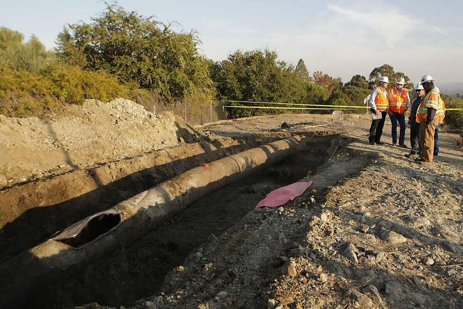 PG&E workers repair a damaged natural gas pipe in Woodside, Calif., on Wednesday, Nov. 9, 2011.  The pipe along I-280 burst during a high-pressure water test, revealing a large gouge and weakness heretofore unseen. Photo: Dylan Entelis, The Chronicle