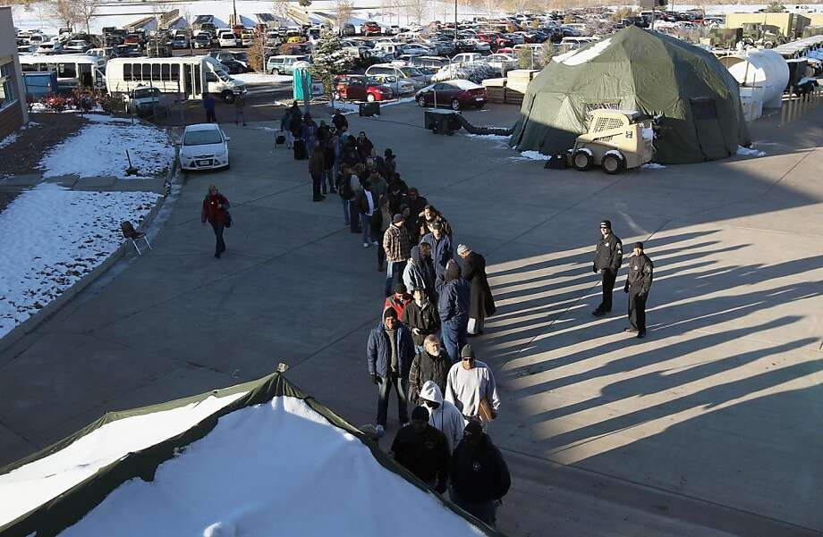 """DENVER, CO - NOVEMBER 03:  Homeless U.S. military veterans stand in line to receive free services at a """"Stand Down"""" event hosted by the Department of Veterans Affairs on November 3, 2011 in Denver, Colorado. A week ahead of Veterans Day, more than 500 homeless veterans were expected to attend the event, where they received free medical care, winter clothing, employment assistance and were able to see a judge to resolve legal issues, among other services. Organizers say the homeless veterans population has surged in recent years with the high national unemployment rate. Stand Down is a military term that means a temporary stop of offensive military action.  (Photo by John Moore/Getty Images) Photo: John Moore, Getty Images"""