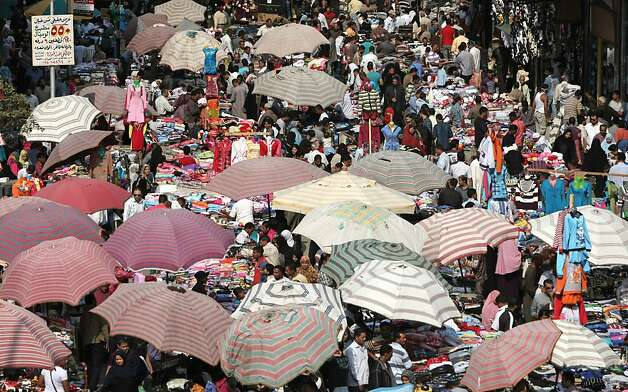 Egyptians crowd a popular market in Cairo on October 31, 2011. According to the United Nations, the global population will hit 7 billion on October 31.  AFP PHOTO/MAHMUD HAMS (Photo credit should read MAHMUD HAMS/AFP/Getty Images) Photo: Mahmud Hams, AFP/Getty Images
