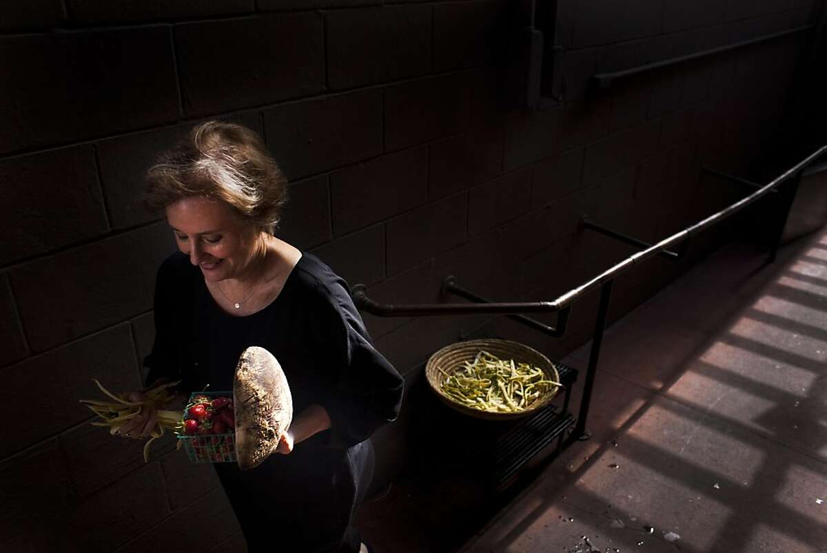 Chez Panisse owner Alice Waters walks out the back door with a few choice prizes before the first reservations arrive at Chez Panisse on Thursday August 4, 2011 in Berkeley Calif.