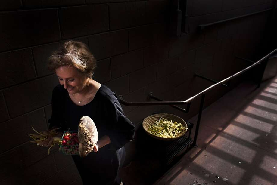 Chez Panisse owner Alice Waters walks out the back door with a few choice prizes before the first reservations arrive at Chez Panisse on Thursday August 4, 2011 in Berkeley Calif. Photo: Mike Kepka, The Chronicle