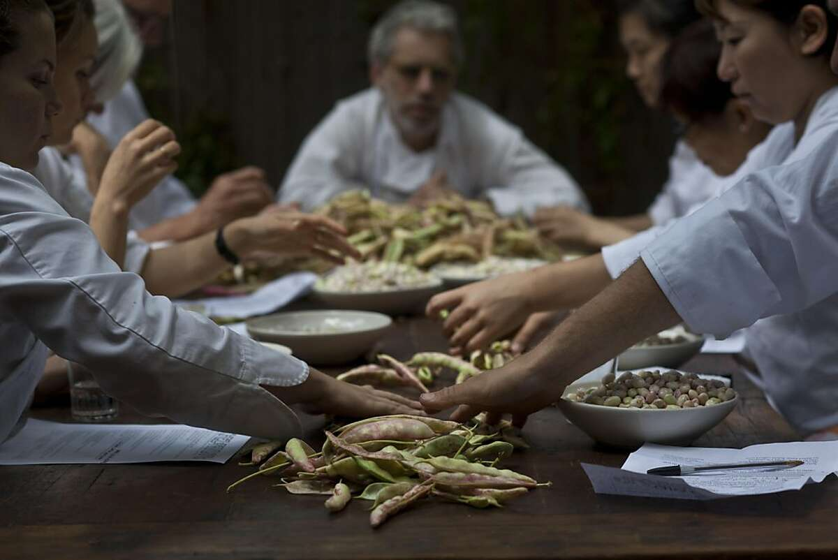 Cooks shell beans during the in the daily chef's meeting in the back of Chez Panisse on Thursday August 4, 2011 in Berkeley Calif.