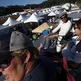 """Jamie Tjahaja, center, Laura Headington, right, and her husband Andrew Headington, left, take a break from volunteering at the American Grilled Cheese Kitchen tent on top of the restaurant's truck at Outside Lands Music and Art Festival in Golden Gate Park in San Francisco, Calif., August 13, 2011.  """"This beats the V.I.P. seats by far,"""" said Andrew Headington."""