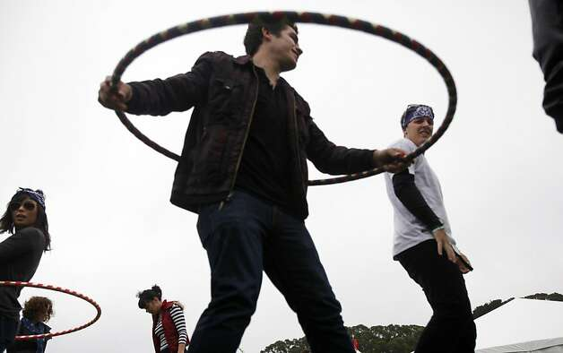 Esteban Terrazas, center, of Monterey Park, Mikey Stragier, right, of West Covina, and Shannon Osaki, left, who was working the KFOG 104.5 tent, play with hula hoops at the radio station's tent at Outside Lands Music and Art Festival in Golden Gate Park in San Francisco, Calif., August 12, 2011. Photo: Sarah Rice, Special To The Chronicle