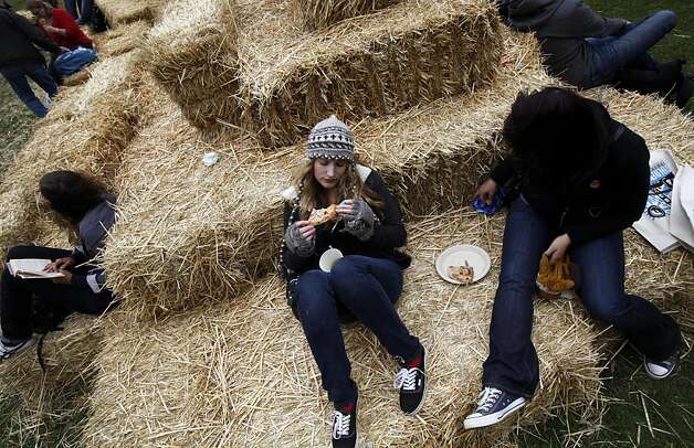 Dana Esposito, center, and Victoria Deane, right, both of Chester, New Jersey, have lunch on a hay bale at Outside Lands Music and Art Festival in Golden Gate Park in San Francisco, Calif., August 12, 2011. Photo: Sarah Rice, Special To The Chronicle