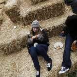 Dana Esposito, center, and Victoria Deane, right, both of Chester, New Jersey, have lunch on a hay bale at Outside Lands Music and Art Festival in Golden Gate Park in San Francisco, Calif., August 12, 2011.