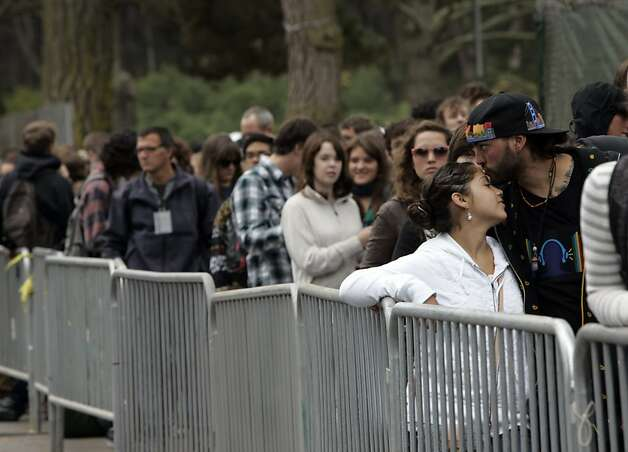 George Ballantyne of Sacramento gives his wife, Maria Luisa Ballantyne, a kiss while waiting for the gates to open on the first day of the Outside Lands Music and Art Festival in Golden Gate Park in San Francisco on Friday. Photo: Sarah Rice, Special To The Chronicle
