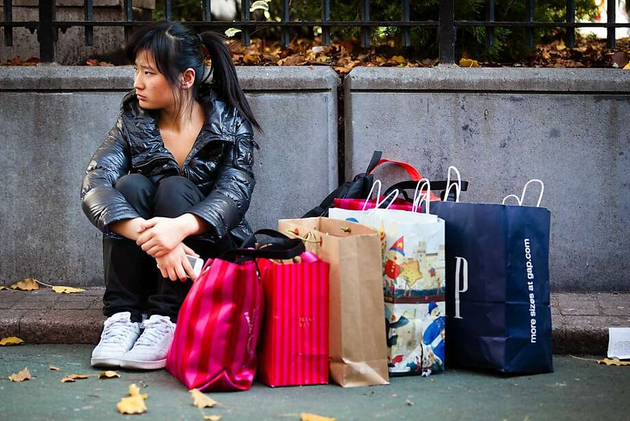 A consumer rests herself and her bags in Herald Square during the busiest shopping day of the year, Friday, Nov. 25, 2011, in New York. Some of the nation's major chain stores opened late Thursday, competing for holiday shoppers on the notoriously busy Black Friday to kick off a period that is crucial for the retail industry. (AP Photo/John Minchillo) Photo: John Minchillo, AP