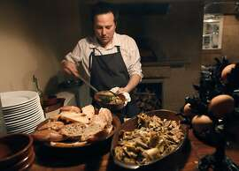 Chef/owner Russell Moore prepares dishes that will be cooked in the wood-fired oved at Camino restaurant in Oakland, Calif., on Wednesday, October 7, 2009. Chef/owner Russell Moore is doing the cooking.