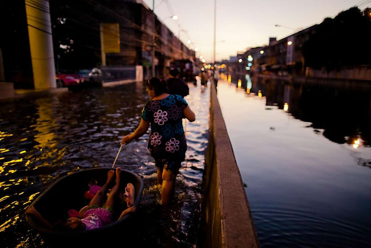 BANGKOK, THAILAND - NOVEMBER 01: A woman pulls her daughter behind her in a small raft as she walks along a flooded street, near to the overflowing Chao Phraya river on November 1, 2011 in Bangkok, Thailand. Around 370 people have died in flood-related incidents since late July according to the Department of Disaster Prevention and Mitigation. Thailand is experiencing the worst flooding in 50 years with damages running as high as USD 6 billion which could increase as the floods swamp Bangkok. (Photo by Daniel Berehulak/Getty Images)