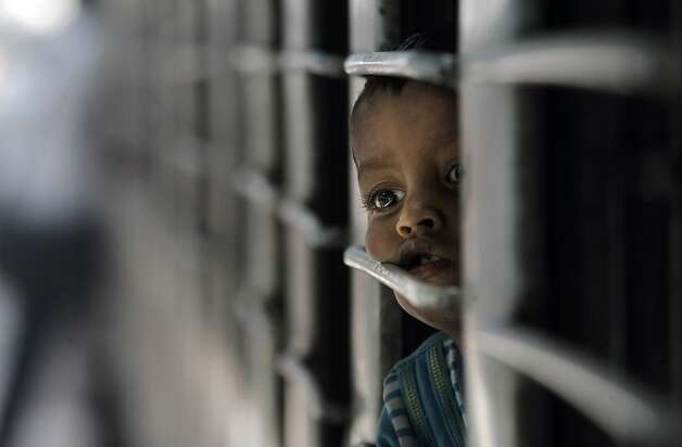 "A child looks out of a window of an over crowded train at the New Delhi railway station in New Delhi, India, Monday, Oct. 31, 2011. According to the U.N. Population Fund, there will be a symbolic ""seven billionth"" baby sharing Earth's land and resources on Oct. 31. Already the second most populous country with 1.2 billion people, India is expected to overtake China around 2030 when its population soars to an estimated 1.6 billion. (AP Photo/Manish Swarup) Photo: Manish Swarup, AP"